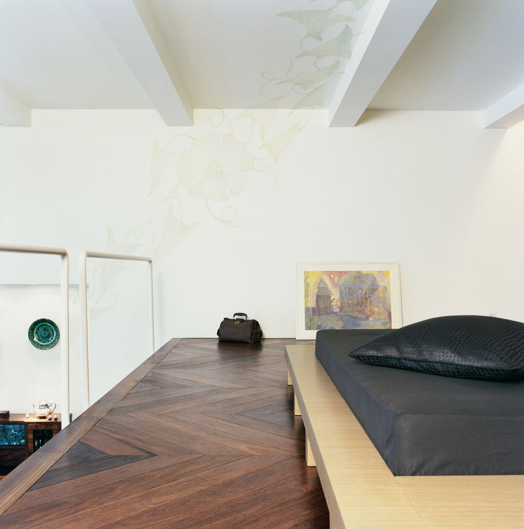 The platform bed was designed by the architect. The pattern on the ceiling was drawn by Rasa Baradinskiene, a local designer, in colored pencil over the off-white paint. Mikulionis and Marcinkeviciute don't worry about slipping through the rails to the li