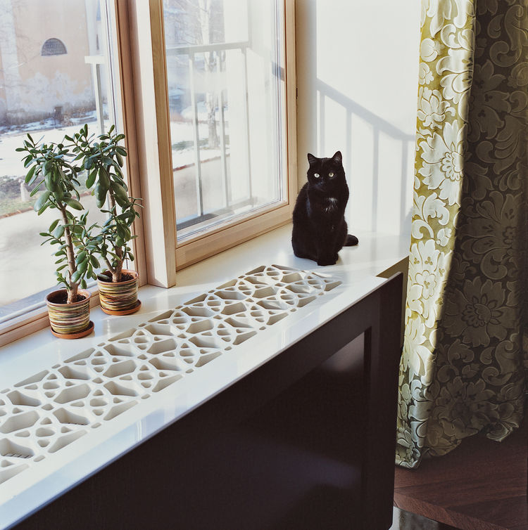 Moby the cat sits on the windowsill, which the architect constructed by cutting a geometric pattern into a thick sheet of MDF, a fiberboard product that's inexpensive, easy to machine, and unrecognizable when coated in white lacquer paint.