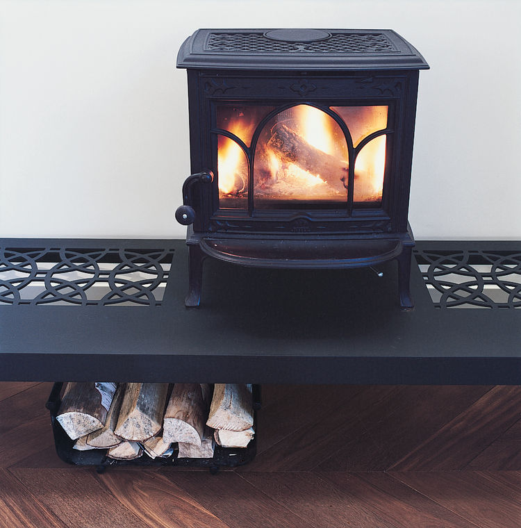 The wood stove roars atop a table designed by the architect.
