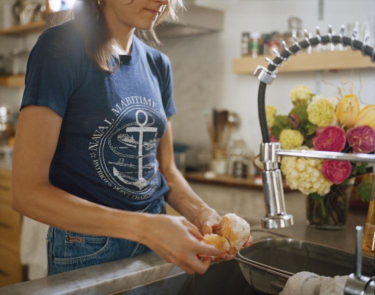 Helen Nissenboim washing produce in the kitchen.