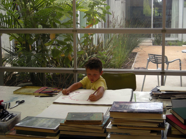 Orlovski and Arato's son at work in dad's studio, to which the architect added a large, roll-up door that when raised, opens the space completely to the backyard patio and main house. The house's dining room is at right; behind the plantings is the master