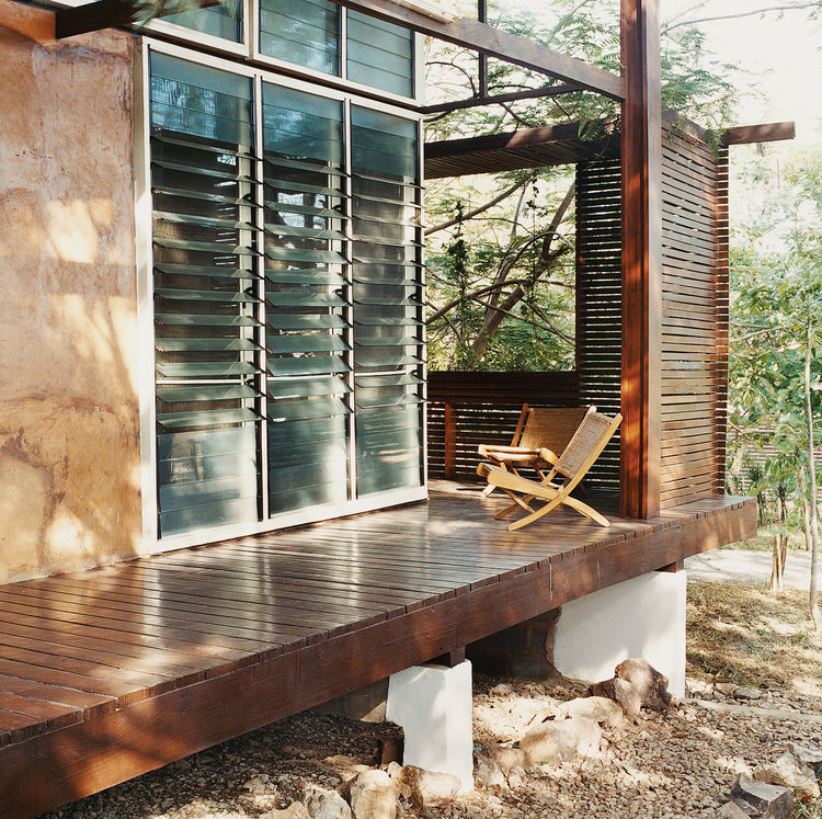 Slatted wooden screens afford privacy and break the short but driving rains that blast the house from the southwest.