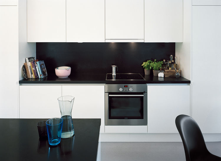 Laminated-MDF cabinetry helps to hide clutter in the kitchen.