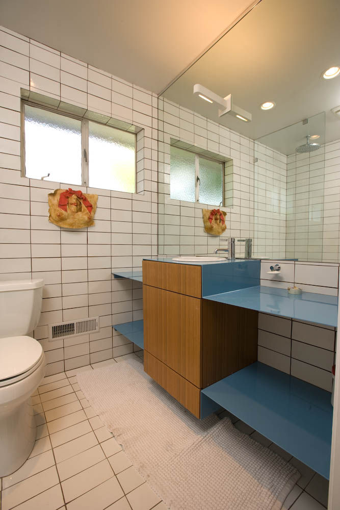 """Popp created wood cabinetry surrounded by another powder-coated steel vanity """"with a punch of blue"""" for the bathroom. In anticipation of the project, he took time to gather key elements, such as the bathroom's Dornbracht faucet, at sale prices."""