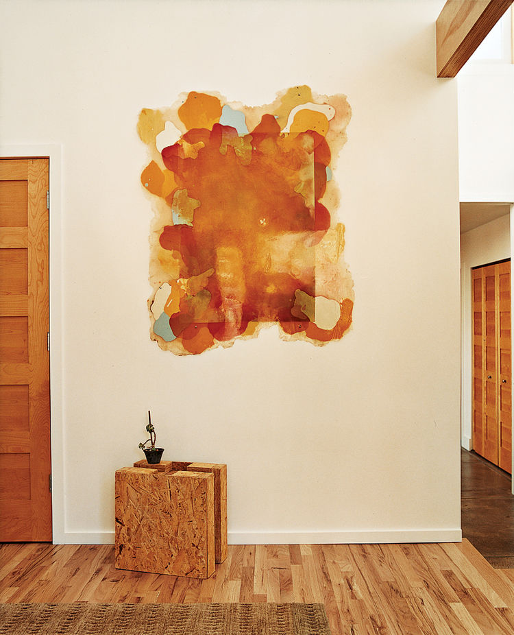 Walking in the front door it's hard to miss the square chunk of compressed-straw paneling—a building material-cum-sculpture that allows visitors to see what the house is made from. Kahn's paintings hang throughout the house, and several of the rugs are he