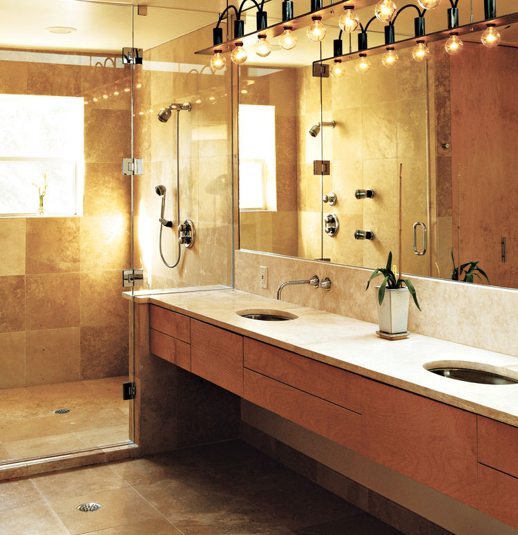"""The master bath is a simple rectangle. """"Like the kitchen, I designed it so that no stuff was laying around,"""" Erik said. The surfaces are natural and subdued; a simple palette of tones, colors, and materials unifies the space. Travertine marble was used on"""
