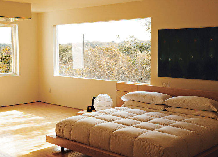 In the third-floor bedroom, horizontal wood-framed casement windows by Pella open out to tree-filled views of Lake Austin and Westlake Hills. Comfortably austere, the only furniture here is the bed, two nightstands, and a marble table for books and candle