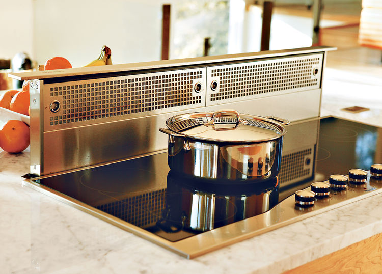 """Because the kitchen is so open, Erik designed it in such a way that there's room for everything from cookbooks to wine racks. Even the Viking stove hood disappears into the counter at the touch of a button. """"People ask if we spend a lot of time cleaning,"""