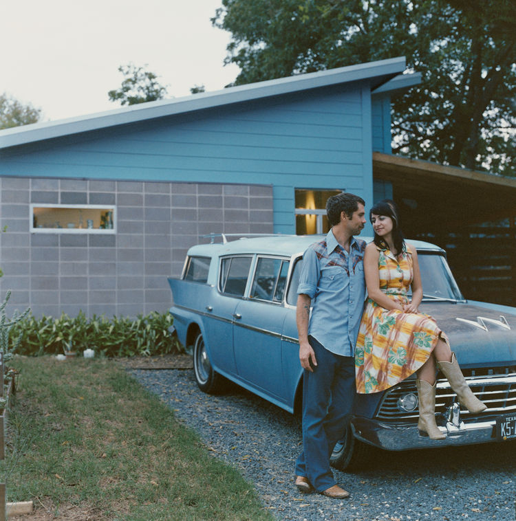 Andy and Regina Rihn lean on their other blue-clad affordable design, a 1958 AMC Rambler Super station wagon, in front of their house in Austin, Texas.