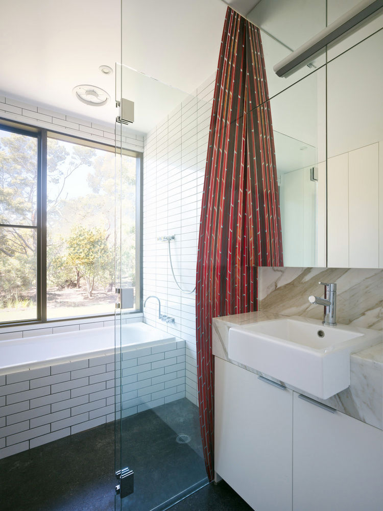 This bathroom, which abuts the kitchen, also houses the laundry, which can be closed off behind tall white doors. Considering how removed the house is from its rural neighbors, bath time privacy is of little concern.