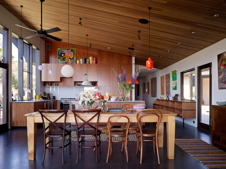 The kitchen, living and dining rooms are the heart of the home. Once you make it down the long corridor you come into this wonderfully open space festooned with dangling lights and a vault of wooden slats. The whole space is well-wrought, but unfussy. I f