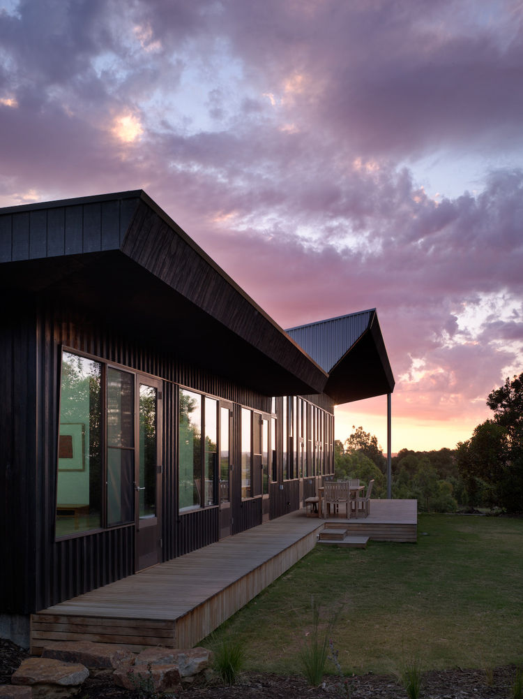 """Darker external colors integrate the house into the shadows of the surrounding bushland,"" Rowan said. ""The courtyard is a lighter color to contrast with the exterior and make it feel a bit more like an interior to be within, even though it's outside."" Th"