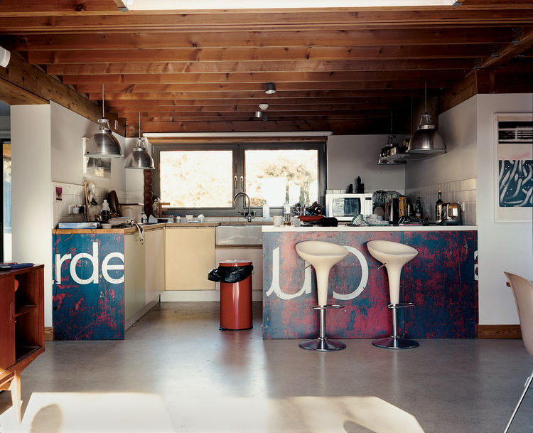 Carver and Carloss's choice of kitchen design by artist friend Neil Jolliffe reflects the couple's eclecticism and playfulness. The kitchen cabinetry draws from the soft pastel shades often seen in English coastal towns. The lighting fixtures are Giant Pe