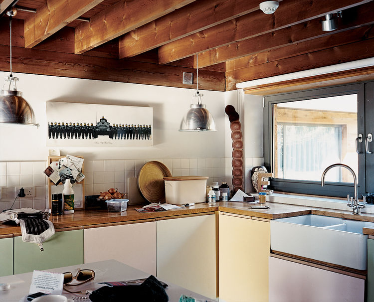 The architects kept the low-beamed ceiling, retaining the house's English countryside charm. The kitchen features custom cabinetry designed by artist Neil Jolliffe. The couple purchased their Banksy prints from the artist's London gallery, Tom Tom.
