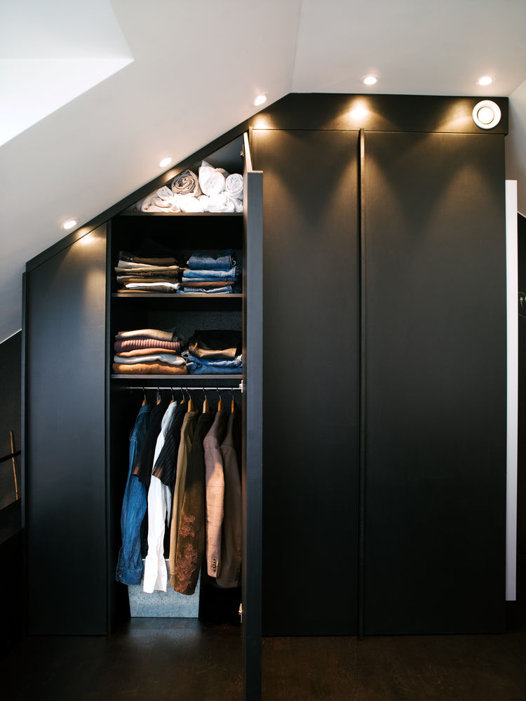 "The apartment's built-in closets are deep and have mirrors on one side. Spotlights set flush overhead provide light and also allow the maximum amount of storage, all the way to the ceiling. Photo by <a href=""http://www.permagnuspersson.com/"">Per Magnus Pe"