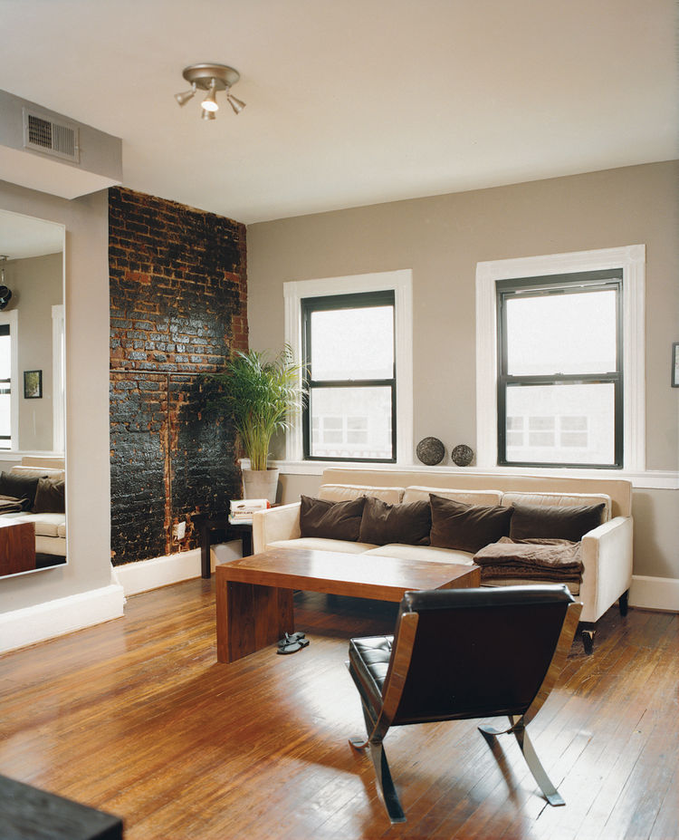 Peeling back plaster and drywall they unearthed beautiful brick walls. They opted to leave them exposed, letting light from the street and a wall of rough-hewn red brick warm up the large living rooms and kitchens. Mazza's living room sofa is from Crate a