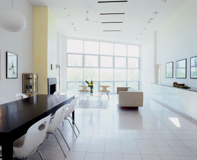 white walls and ceiling window bank modern interior dining room and living room of New York home