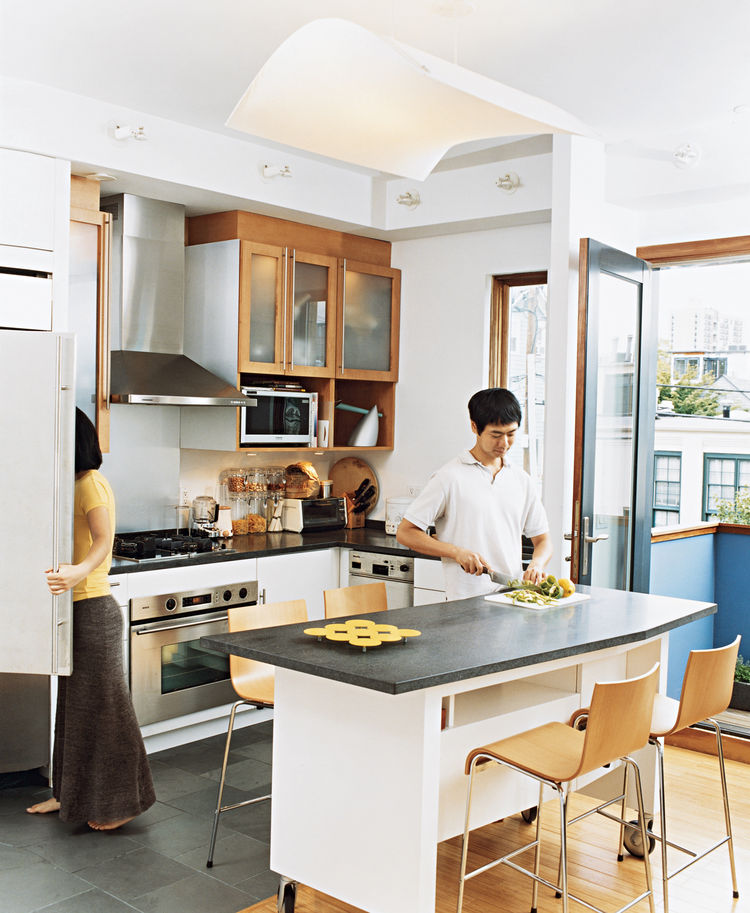 Avid cooks, Jinhee and John spend part of every day around their custom-built kitchen  island, surrounded by Compasso d'Oro barstools. An edamame plant on their patio occasionally provides leaves for Korean dishes.
