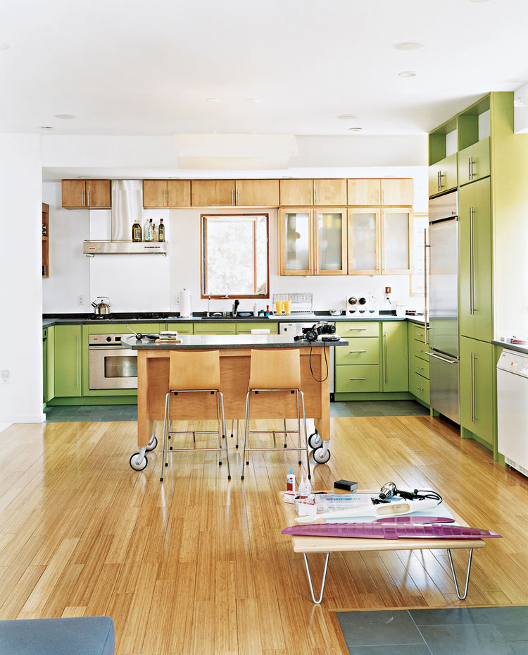 Knowing that Andy's multi-tasking begets clutter, John provided him with plenty of cabinets. By making very particular requests of The Home Depot—asking for irregular-sized doors and painting them electric green—John defied the generic look of big-box cab