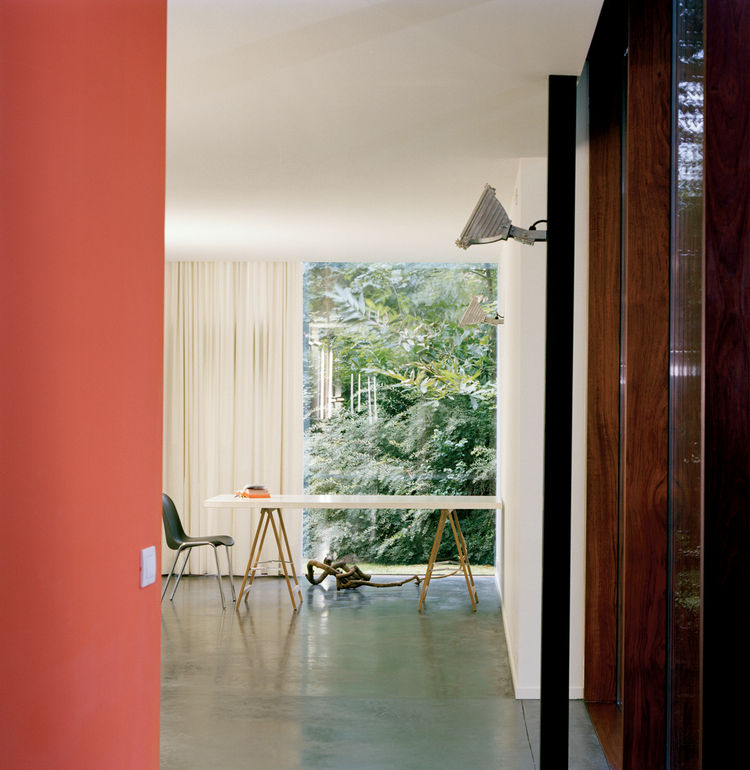 Van Everbroeck's home office occupies the end of one arm of the building. An industrial outdoor light fixture is mounted on a black-painted steel post. The orange of the back wall was chosen to work with the glowing rays of the sunset and the silhouetted,
