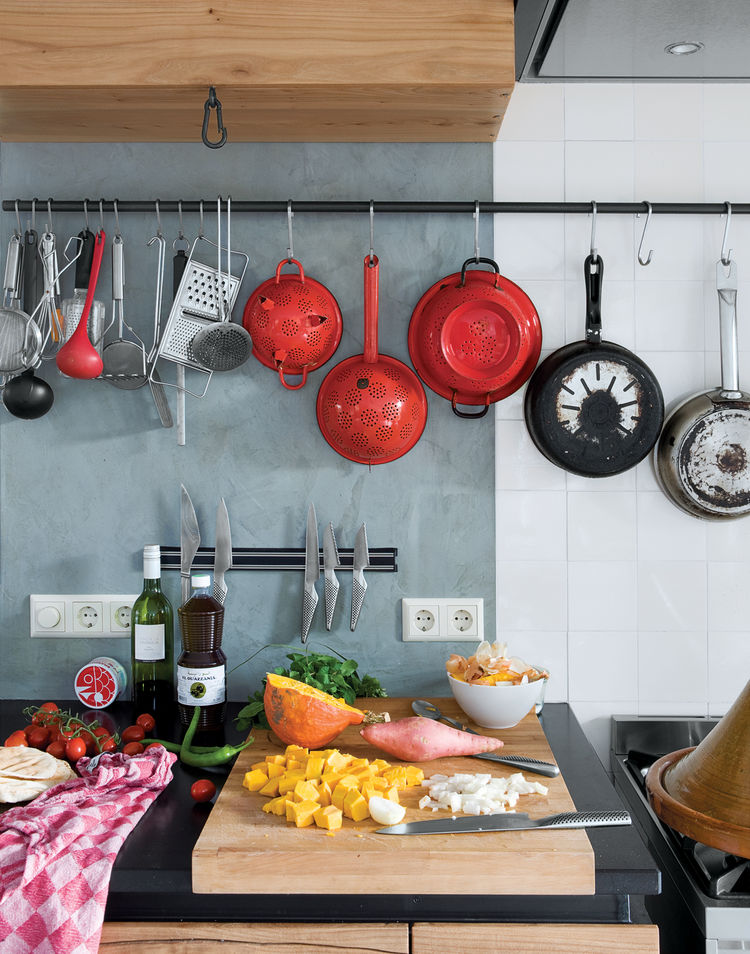 """Black stone worktops, waxed concrete walls, and the traditional rustic tiles (called """"witjes"""") give textural and tonal variety and offset the warm woody tones that dominate this kitchen. The rustic theme is continued in the iron hooks and bars—simple but"""