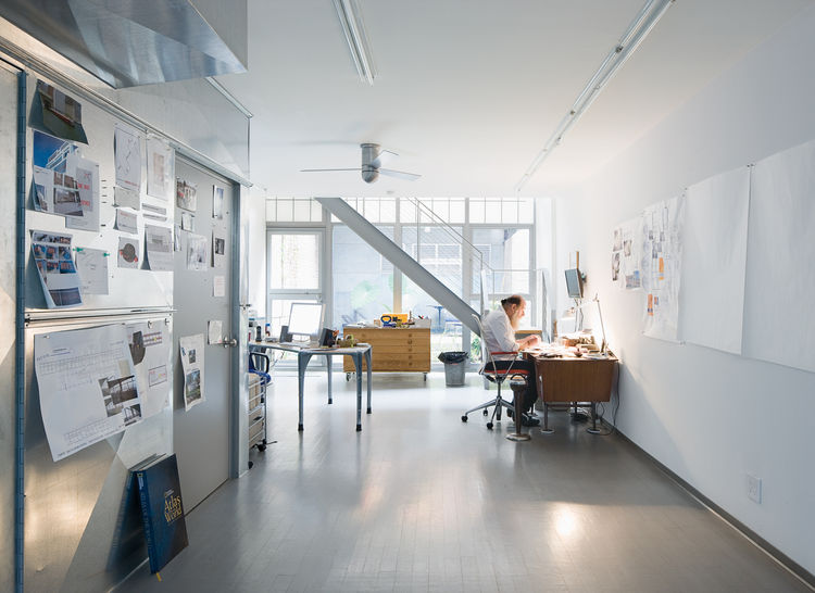 Lawrence Weiner sits at his daylit desk. The bare walls are perfect for tacking  up new projects, and the steel ductwork gives the space an industrious feel.