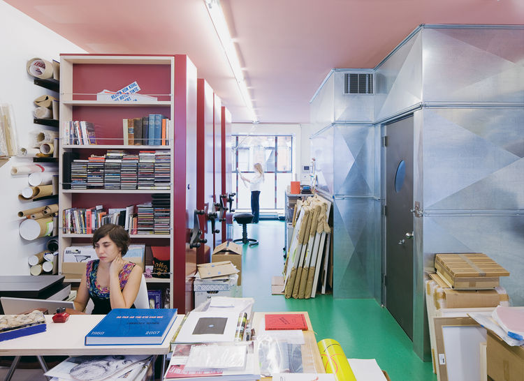 The couple's archival photographer Alyssa Gorelick sits in front of Lawrence's sliding red storage units while Alice reviews some papers in the background.