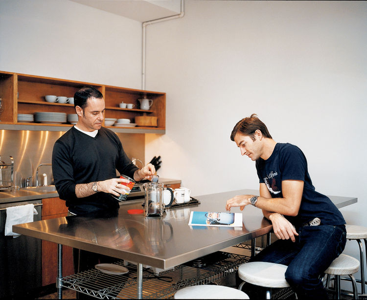 Weinstein and partner Eric Hensley at the stainless steel work table in the kitchen. The table, pantry doors, and sink backsplash are all made from simple wood forms the architects had wrapped by a metal fabricator—something anyone can do.
