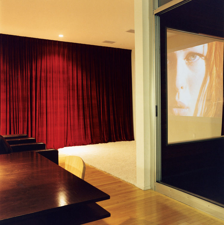 The kitchen transitions into the living room, which transforms easily into a home theater when the heavy red drapes are pulled tightly shut. The home theater system features a projector by Sharp.