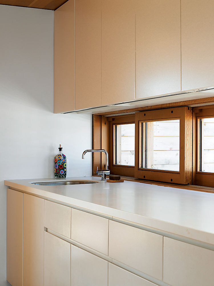"Upstairs in the Floating House, building codes didn't allow a full kitchen, but a galley kitchenette continues the compound's simple palette of white and Douglas fir. ""I love how understated it is,"" says Worple."