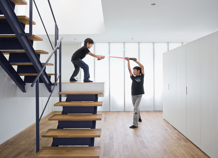 The open-tread stair leading from the garage to the second-floor living room sets the stage for a Star Wars–style duel.