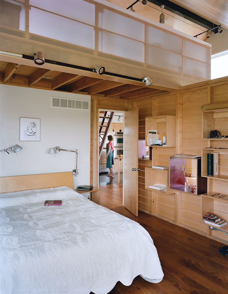 The slatted wall that divides the sleeping and living quarters has maple-ply boxed shelves that can be rearranged.