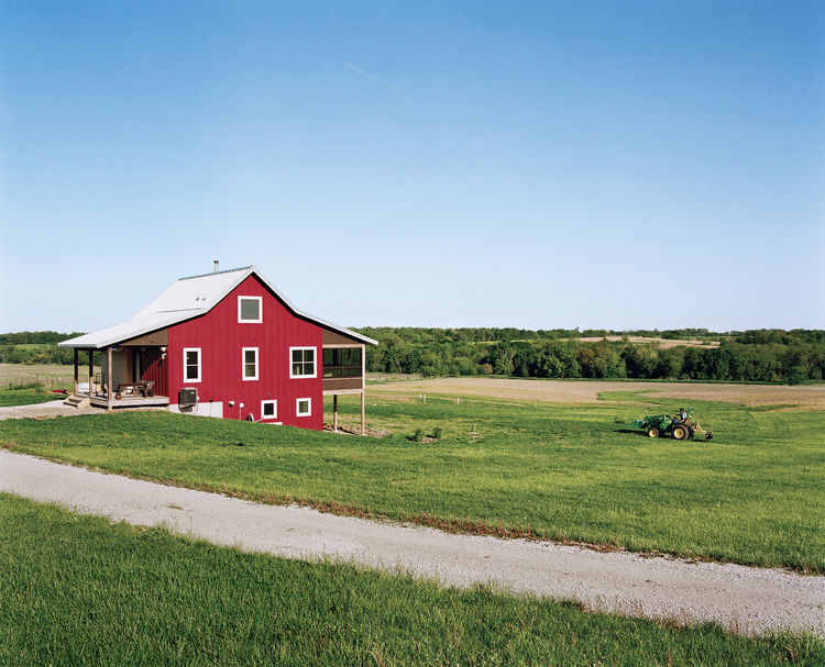 Geoff and Joanna Mouming's compact modern farmhouse is the first permanent structure at Yum Yum Farm in Wellman, Iowa. On the field that stretches out before  it, organic vegetables will soon make attentive farmers of the Moumings. The benches on their en