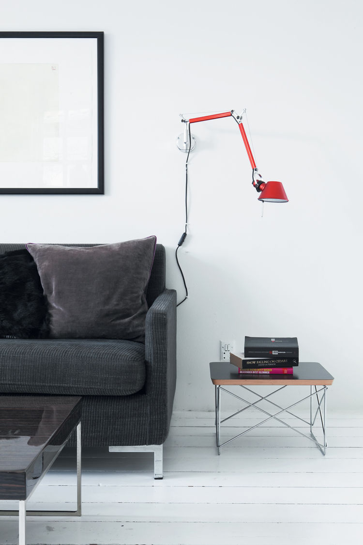 Minimalist living room with red wall lamp and Eames side table