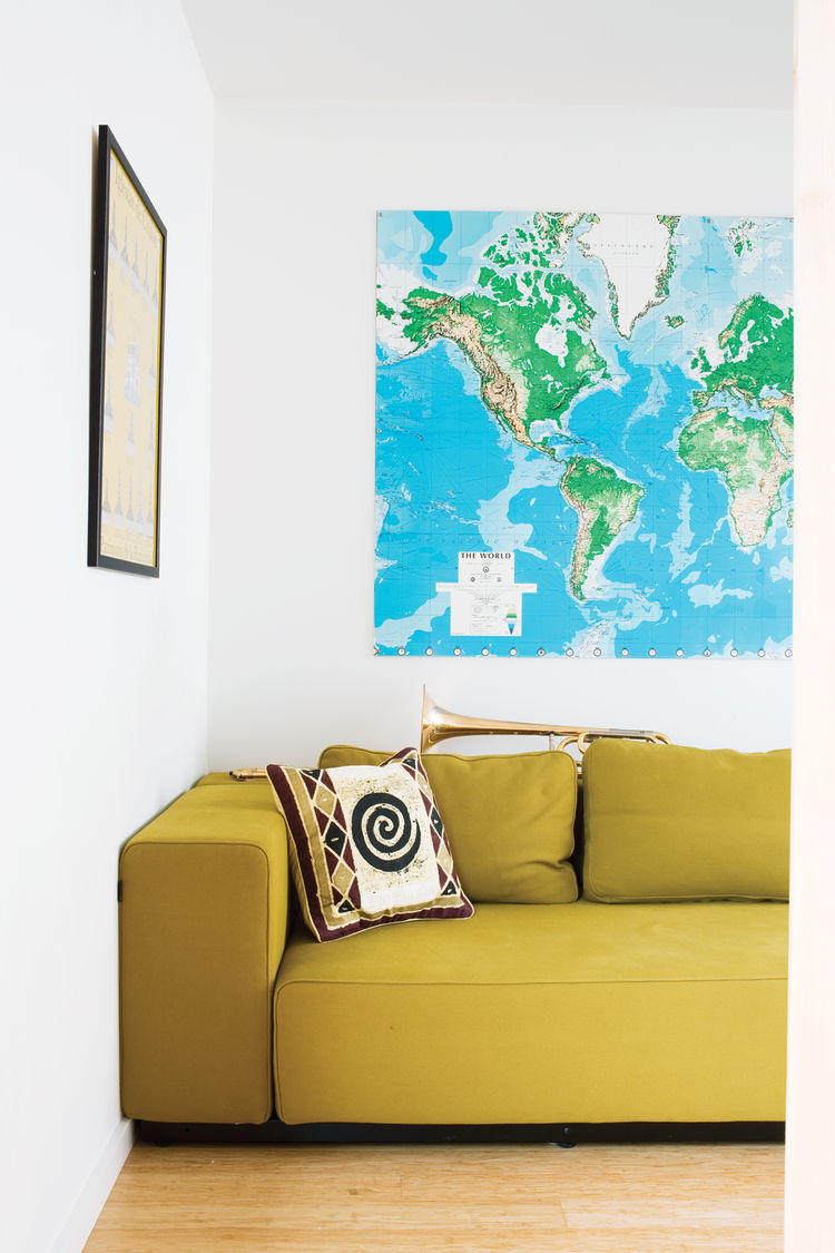 Lofty living room with green sofa and world map wall poster