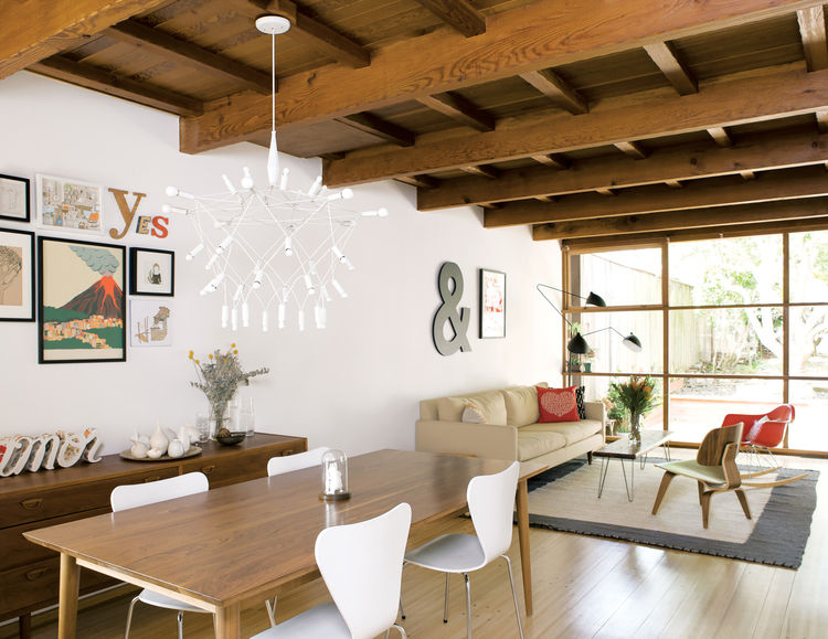 Modern dining and living room with exposed wooden rafters