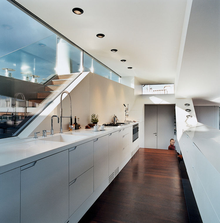 The kitchen window looks out to stairs that lead up to a small roof terrace. The kitchen faucet is by Dornbracht. The recessed lighting is by Guzzini.