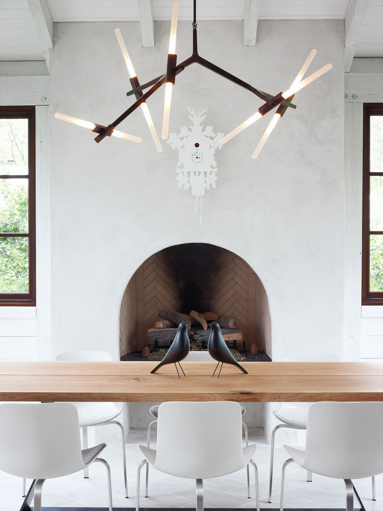 modern dining space with chandelier and Eames house birds