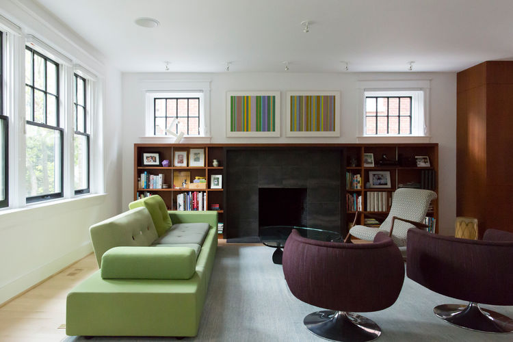 Modern living room design with green sofa, purple lounge chairs, and grey carpet