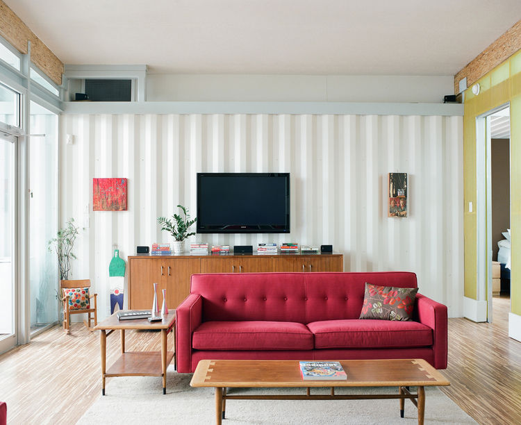 The couple had a big flat-screen TV but didn't want it to be the focus of the living room. Placed on the wall behind one of the red couches, it hangs quietly without drawing attention to itself but is in perfect position for TV-watching from the second co