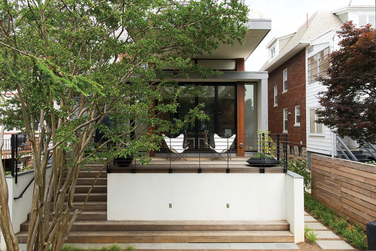 Modern home with wood deck and white butterfly chairs