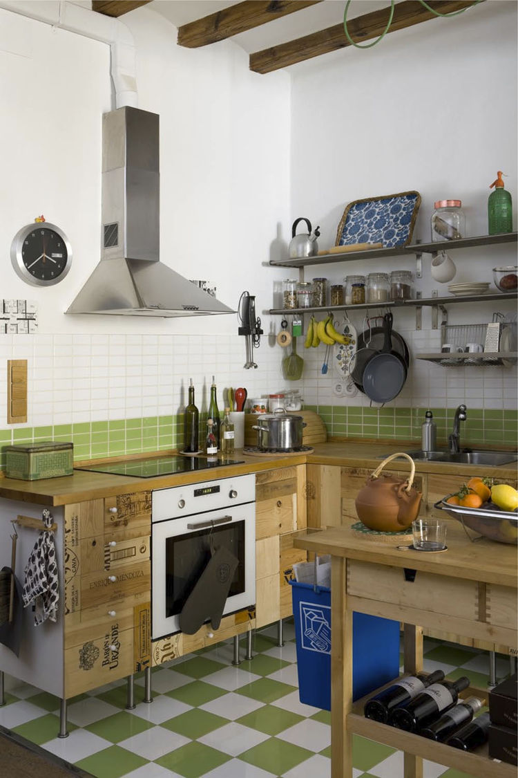 The kitchen cupboards were crafted from recycled wooden wine boxes, and the countertop is untreated wood certified by the Forest Stewardship Council (FSC) from Ikea. The green-and-white tiles are from a local company, TAU Cerámica.