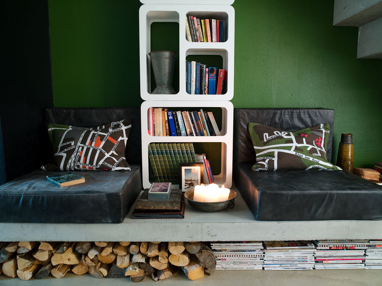 "The reading corner can be turned into an extra bed. Schonning designed the leather poufs himself, and made the cushions from an Ikea carpet. Under the concrete slab there is room for wood, books and newspapers. Photo by <a href=""http://www.permagnuspersso"