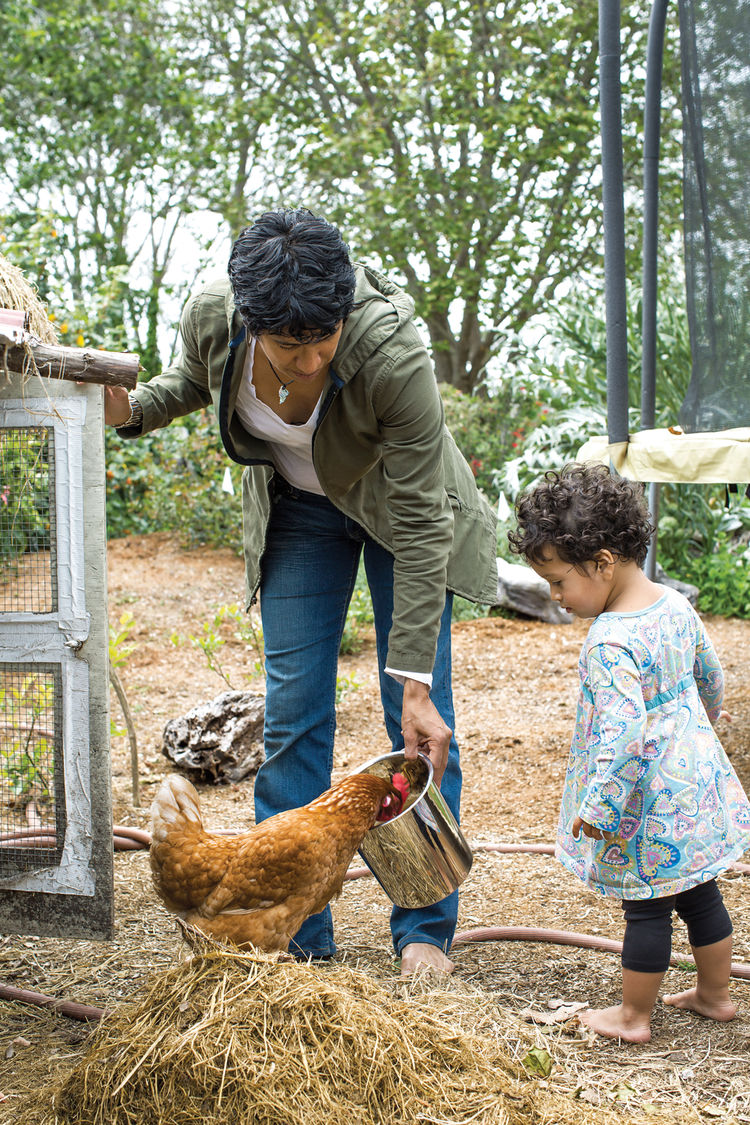 Mother and daughter feeding a chicken outside