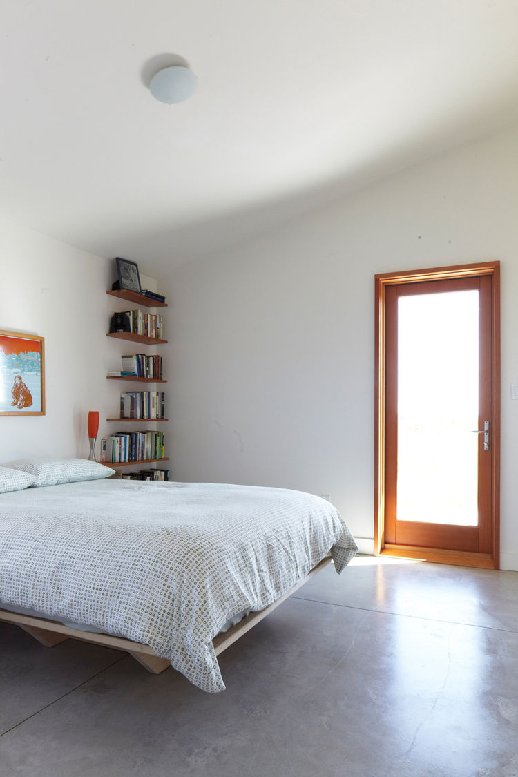 Modern master bedroom with stone flooring and wood framed door