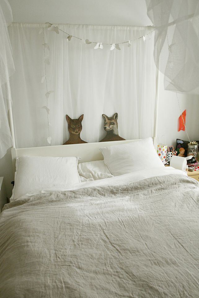 Mae's room with linen bedding and cat and fox portraits.