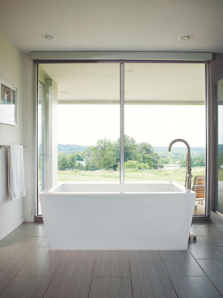 Modern master bedroom with freestanding acrylic bathtub