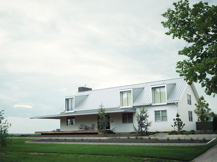 Outdoor view of modern farmhouse with metal roof