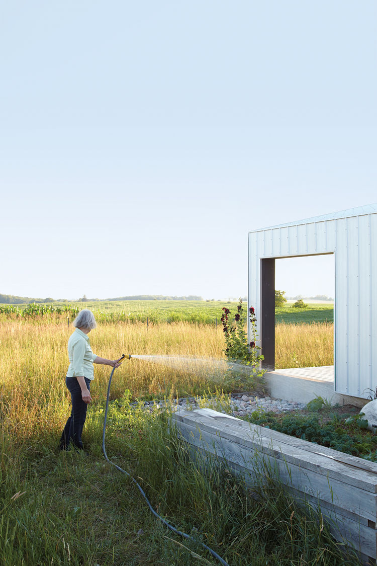 Homeowner watering outdoor plants