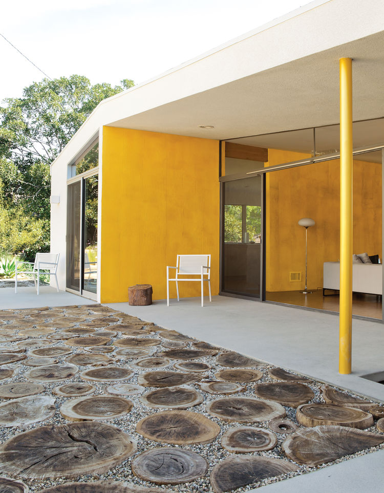 Modern outdoor area with orange yellow wall and stump floor